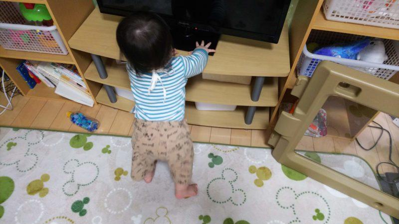 テレビ台につかまり立ちをする息子